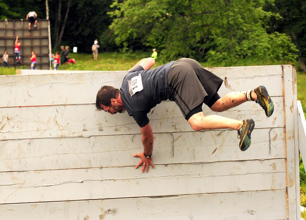Todd Edwards flops over a short climbing wall in Saturday's race. Edwards finished 13th overall in a field of 140 who completed the 4-plus mile course. (Enterprise photo — Lou Reuter)