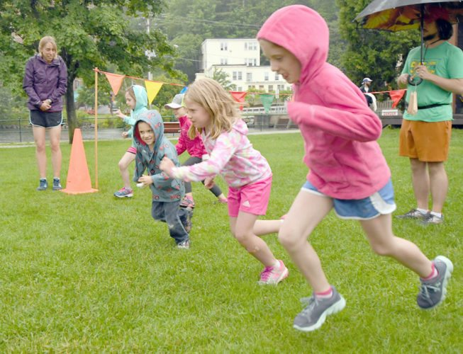 Youngsters leave the start line on a rainy evening on June 29 to begin the first Saranac Lake Fun Run of the summer. The weather kept turnout low that night, but the next two Thursday night events saw crowded fields. (Enterprise photo — Lou Reuter)
