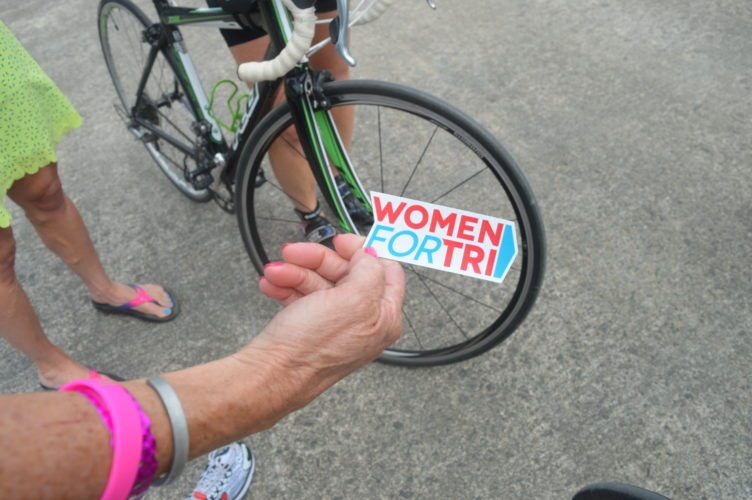 "Moira Horan of Spring Lake Heights, New Jersey holds up a sticker from the ""Women For Tri"" international group, which has more than 30,000 Facebook members worldwide. (Enterprise photo — Antonio Olivero)"