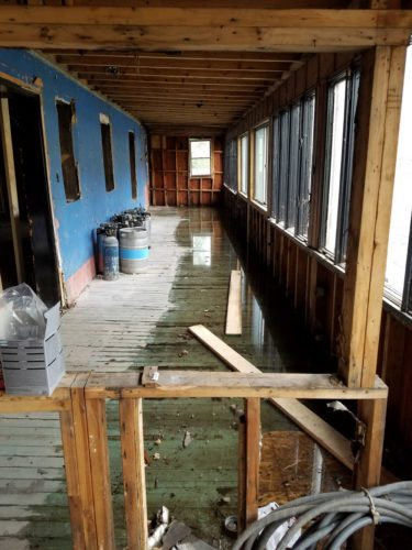 High water from the Saranac River partly covers the floor of a porch at the former Dew Drop Inn building July 1. The flood damage was negligible, co-owner Calli Shelton said. (Photo provided — Calli Shelton)
