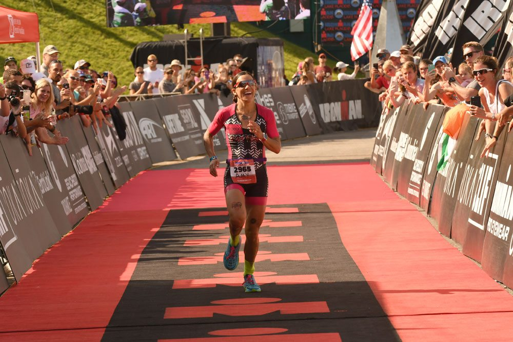 Tupper Lake's Amy Farrell smiles while running to the finish like as the first woman to cross the finish line at the 19th annual Ironman Lake Placid triathlon Sunday. Farrell successfully defended her women's amateur title. (Enterprise photo — Lou Reuter)