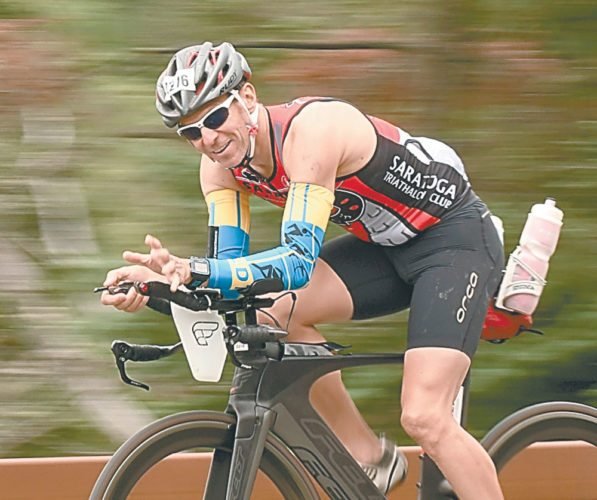 Brian Dillenbeck of Alplaus, New York, rides along state Route 73 near the Olympic ski jumps early in his second 56-mile bike leg during Sunday's 19th annual Ironman Lake Placid race. (Enterprise photo — Lou Reuter)