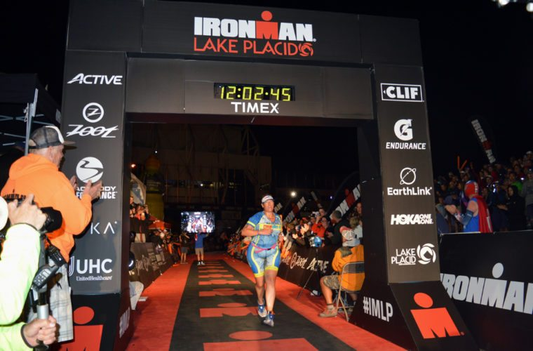 "Michele Stryeski of Bristol, Connecticut charges toward the finish line at the Olympic Speedskating Oval in Lake Placid at 12:02 a.m. Monday morning, the final person who was brought in by ""The Voice of Ironman"" Mike Reilly after completing the 140.6-mile triathlon. (Enterprise photo — Antonio Olivero)"