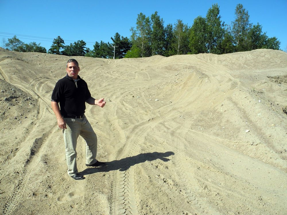 Tupper Lake village Code Enforcement Officer Peter Edwards stands among ATV tracks on sand mounds at the town garage. The sand is used to improve traction on roads in winter, but local ATV riders use it as a playground. (Enterprise photo — Aaron Cerbone)