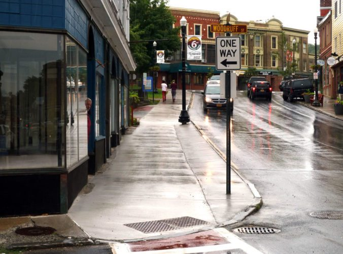 Rain on Monday trickles down the newly finished sidewalk on Broadway between Woodruff Street and Main Street in Saranac Lake. The sidewalk is one of the many local construction projects to be delayed. (Enterprise photo — Kevin Shea)