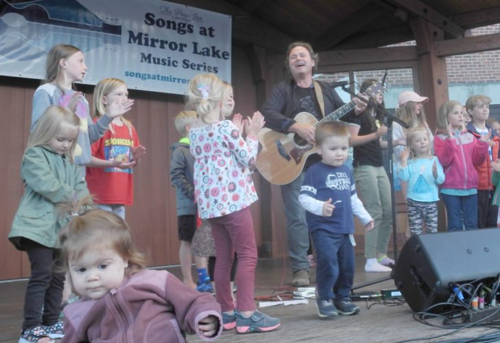 Children join singer/songwriter Martin Sexton on stage Tuesday night in Mid's Park in Lake Placid during the Songs at Mirror Lake music series.  (Enterprise photo — Aaron Cerbone)