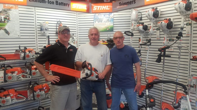 From left, Dick Branch of Sturdy Supply in Saranac Lake, stands with Mike Kinville, who won a chainsaw that the local business raffled off to support the Red Wilcox Memorial Scholarship Fund. Craig Wilcox, Red's son, stands at right. (Photo provided)