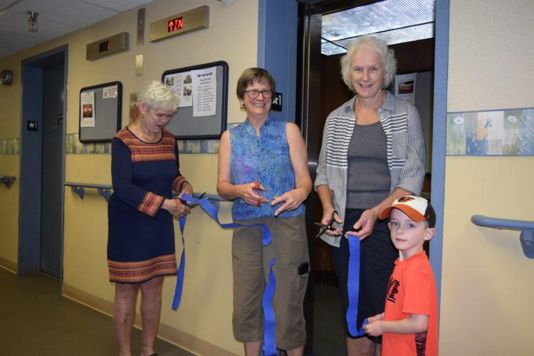 From left, Harrietstown Housing Authority Chairwoman Emily Fogarty, Executive Director Sarah Clarkin, town of Harrietstown Councilwoman Patricia Meagher and her grandson Jack help cut the ribbon Wednesday on the new elevators at the Lake Flower Apartments on Kiwassa Road. (Enterprise photo — Chris Knight)