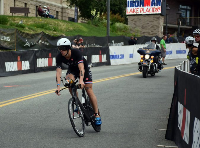 An Ironman triathlete bikes down Main Street, Lake Placid during Sunday's race, followed by a state  trooper on a motorcycle helping maintain safety. Several roads are closed for the annual triathlon. (Enterprise photo — Justin A. Levine)