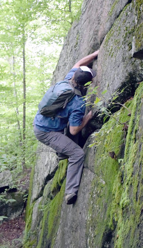 Will Roth of Saranac Lake makes the first move on a bouldering challenge he developed on Baker Mountain. (Enterprise photo — Justin A. Levine)