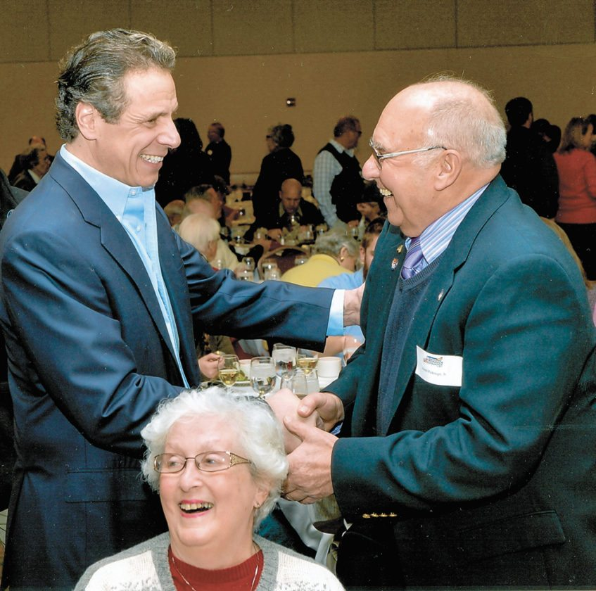 Fellow Democrats exchange pleasantries as Joe Pickreign, right, greets New York Gov. Andrew Cuomo during an Adirondack Challege post-event dinner. Pickreign's wife Shirley is seated below. (Photo provided)