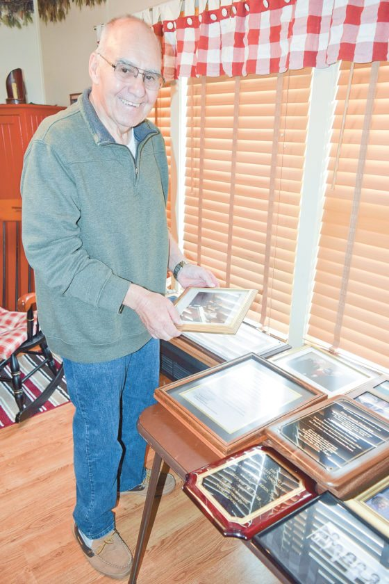 Joe Pickreign talks earlier this month about his decades of involvement in politics while looking at old pictures and awards he's received at his home in Lake Clear. (Enterprise photo — Chris Knight)