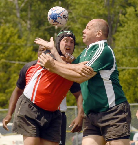 Two players battle for the ball during Friday afternoon's over-50 division Can-Am Rugby Tournament game between the Mountaineers Old Boys and Lockport at Petrova Middle School in Saranac Lake. (Enterprise photo — Lou Reuter)