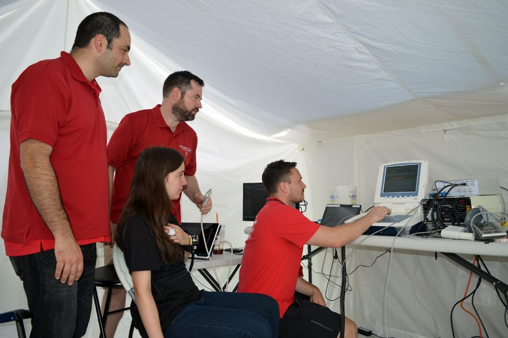 Allan Knox, far right, a doctoral fellow at Rutgers University Medical School in Newark, New Jersey, observes a monitor as he and other members of the Rutgers and Western Sydney (Australia) University research teams test out a prototype shirt worn by Daniella Serrador, seated, designed to measure blood flow of rugby players who just suffered head trauma at the Can-Am Rugby Tournament in Saranac Lake. Also pictured are Dr. Gaetano Gargiulo, far left, and Dr. Paul Breen, rear. (Enterprise photo — Antonio Olivero)