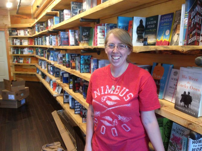 Jessie Fischer of Saranac Lake smiles Friday evening as she puts books on the shelves of the Book Nook, her new Saranac Lake business that she hopes to have ready to open Monday, or soon thereafter. The Book Nook is located in downtown Saranac Lake on Broadway next to Borracho Taco, which is owned by Fischer's fiance Ryan Davis. The shop will sell new books in a variety of genres, filling a void in Saranac Lake, which has not had a bookstore since Moose Maple Books & More closed a few months ago. (Enterprise photo — Peter Crowley)