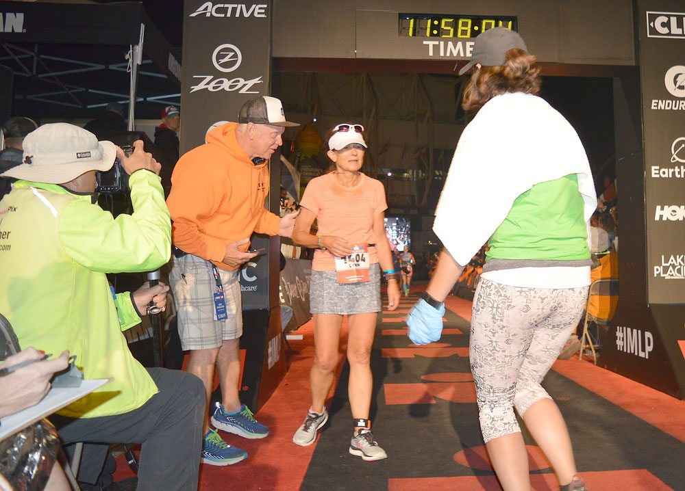Ironman Lake Placid triathlete Lynn Byrne of Credco, Pennsylvania, is greeted after she crosses the finish line Sunday, just before the midnight cutoff. (Enterprise photo — Antonio Olivero)