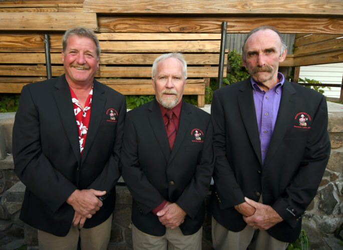 "From the left, Jay Annis, Leo Demong and Mike ""Beef"" Bevilacqua pose in their new Mountaineers rugby attire after a ceremony Friday at the Waterhole in Saranac Lake. The three were chosen as this year's ""Black Jacket"" recipients, an honor that signifies hall of fame status for club members during its 46-year history. The reception hosted by the Mountaineers Rugby Club took place following the first day of action at the 44th annual Can-Am Rugby Tournament. (Enterprise photo — Lou Reuter)"