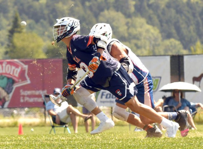 Opponents battle for the ball as grass flies in a match Tuesday between the FCA National High School team and 3rd National in the boys 2018-2019 Gold division at the Lake Placid Summit Classic lacrosse tournament. (Enterprise photo — Lou Reuter)