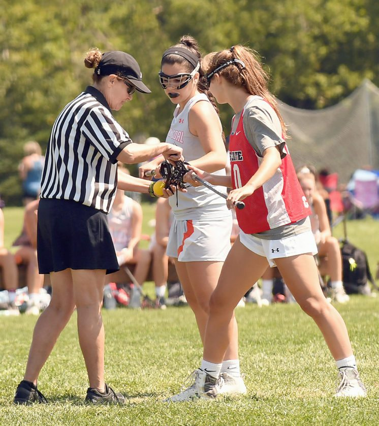 An official gets two opponents set for a faceoff during a girls game Tuesday in the Lake Placid Summit lacrosse tournament at the North Elba Athletic Fields.