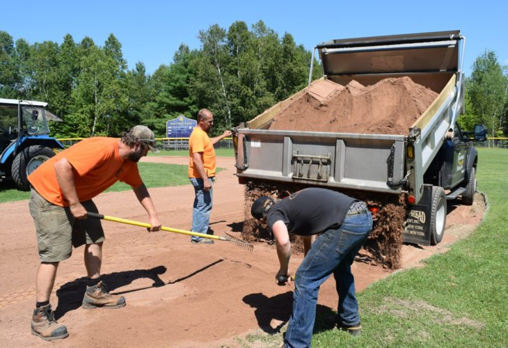 From left, Matt Wolter and Steve Huyck of the Saranac Lake Civic Center and Harrietstown Councilman Ed Goetz rake a new composite clay material into the infield of Elks Field in Saranac Lake. Standing at the back of the truck is Dan Scott of the Saranac Lake Central School District. (Enterprise photo — Chris Knight)