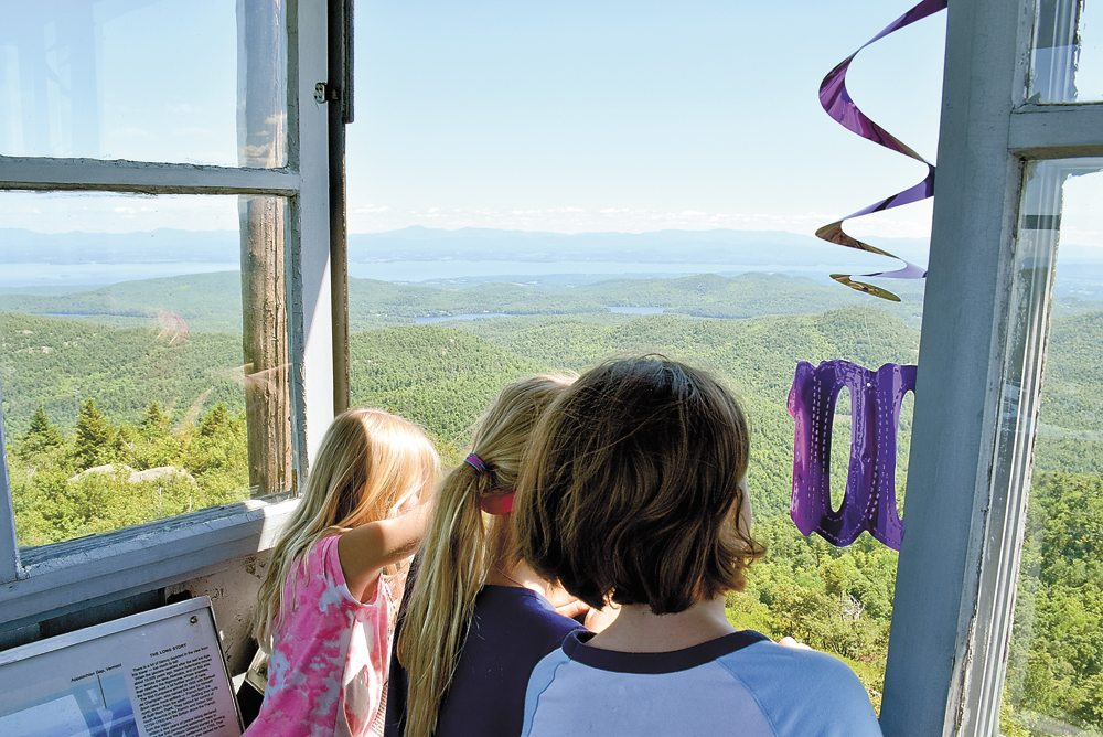 Three young girls take in the view of the Green Mountains and the Champlain Valley from the cab of the restored Poke-O-Moonshine tower last Sunday during the 100th anniversary celebration of the tower.  (Enterprise photo — Justin A. Levine)