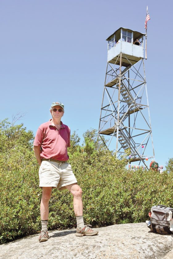David Thomas-Train, who spearheads the Friends of Poke-O-Moonshine group, poses in front of the restored fire tower last Sunday. (Enterprise photo — Justin A. Levine)