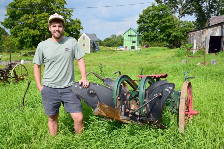 Alex Caskey poses for a photo Monday next to old farming equipment at Reber Rock Farm in Essex. (Enterprise photo — Justin A. Levine)