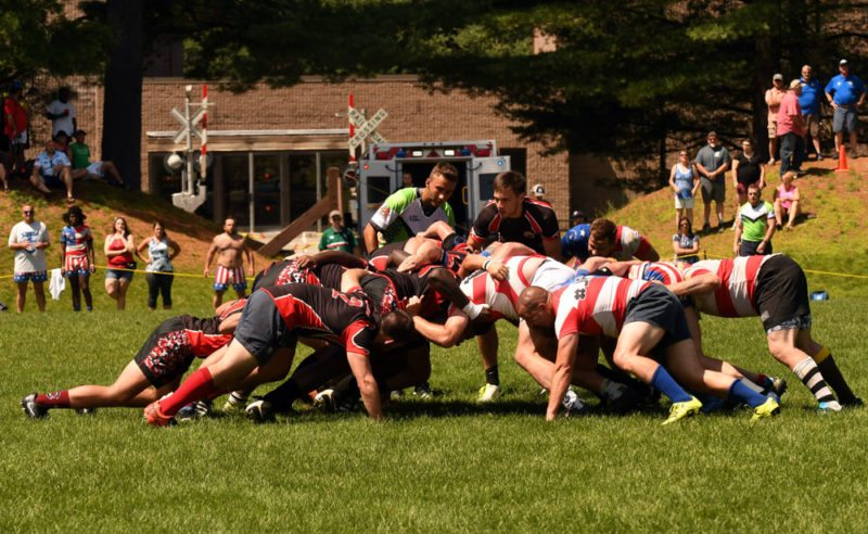 With an ambulance standing by in the background in case of injury, the Saranac Lake Mountaineers Rugby Club, at left, faces off against the East Side Hyenas Sunday in the Can-Am Rugby Tournament's social division championship match at North Country Community College in Saranac Lake. The Mountaineers won 36-32 to claim their first social division title in the tournament's 44-year history. (Enterprise photo — Lou Reuter)