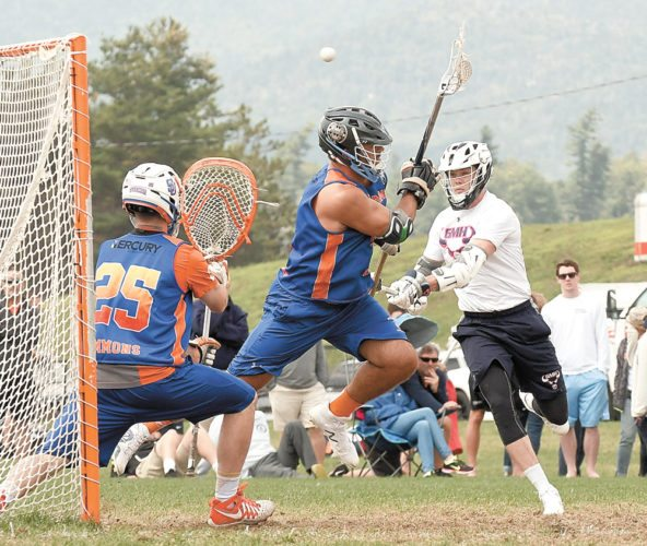 While a teammate applies defensive pressure, Burning Orange goalie Dom Lamolinara gets set to make a save on a shot by a GMH opponent during the first half of Sunday's men's 18-and-over gold championship game in the 28th annual Lake Placid Summit Classic lacrosse tournament. Burning Orange won 8-6 in the final match of the tournament. (Enterprise photo — Lou Reuter)