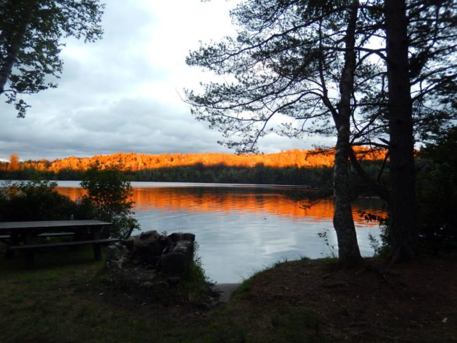 The sunset is reflected on trees Sunday evening at Fish Creek Campground. (Photo provided — Katie Bradford Hall)