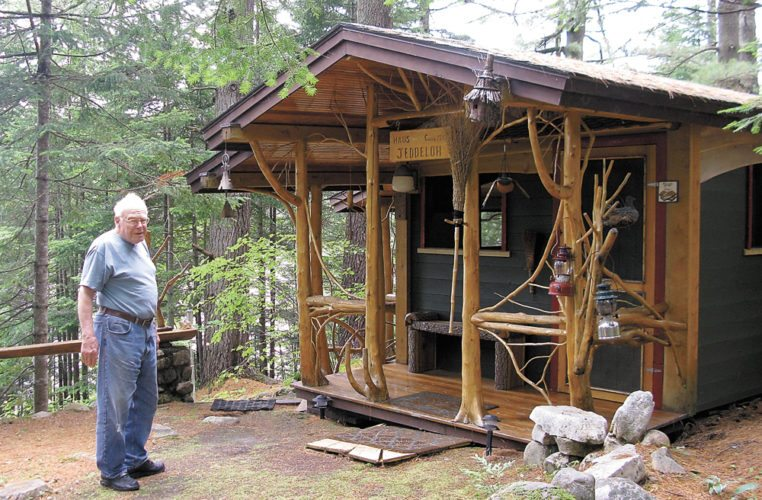 "Don Busch stands next to the ""Clubhouse,"" a cabin built in 1935 by the Jeddeloh family that used to live on the property he now owns in Rainbow Lake called Entayant Gardens.  (Enterprise photo — Emily R. Luxford)"