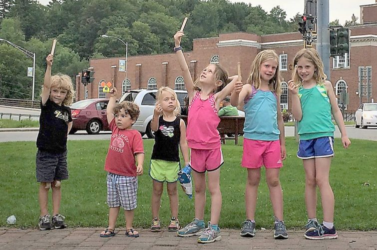 """Saranac Lake Fun Run volunteers Simon Langdon, Tennessee Carr, Annaliese Goff, Lena Shoemaker, Karrissa Holmes and Kaylee Holmes help by handing out """"place sticks"""" during Thursday's adult races in Riverside Park. (Provided photo — Rob Carr)"""