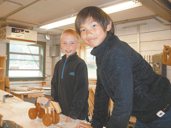 Campers pose in the wood shop with a wooden horse at Camp Treetops. (Enterprise photo — Dana Hatton)