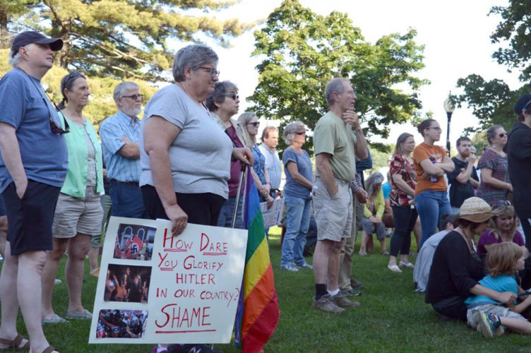 """Tri-Laker residents convened in Riverside Park in Saranac Lake Monday evening to listen to a speaker in the bandshell during a """"Stand in Solidarity with Charlottesville"""" event in the wake of this weekend's deadly Charlottesville rally, where one person died and many more were injured. (Enterprise photo — Antonio Olivero)"""