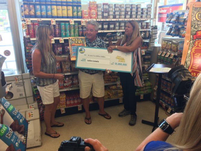 Lottery winner John Lewis poses with his girlfriend Mary, mother Pat Lewis and an oversized check Tuesday at Tops supermarket on Church Street in Saranac Lake, where he bought his winning ticket. (Photo provided — Tops Friendly Markets)