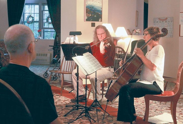 Gregor Kitzis and Kate Dillingham of the Ouluska Pass Chamber Ensemble play for residents of the Saranac Village at Will Rogers on Monday. (Enterprise photo — Aaron Cerbone)