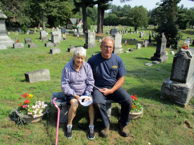 "Natalie Leduc and Pine Ridge Cemetery Board President Mike Madden sit Monday afternoon on a bench that the cemetery board dedicated to Leduc and Kathryn ""Kitty"" Peightal, two of the site's most dedicated volunteers. (Photo provided — Kathy Merritt)"