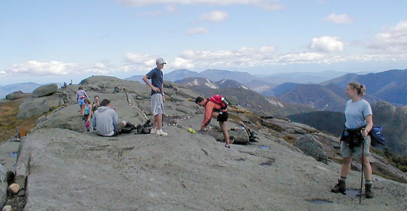 Hikers take a moment to enjoy the summit of Mount Marcy. (Photo — Joe Hackett)