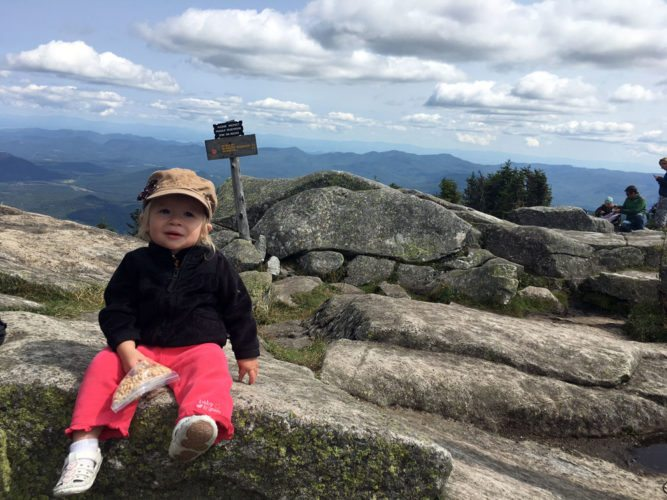 With a bag of Cheerios in hand, 15-month-old  Victoria Young of Buffalo sits at the summit of the 4,867-foot Whiteface Mountain Saturday after trekking with her family up the short but rocky and steep trail from the castle at the shoulder of Whiteface's summit to the mountain's true summit. (Enterprise photo — Antonio Olivero)