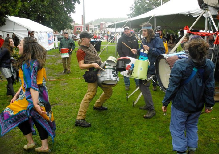 Kyle Murray, center, and the rest of Bucket Ruckus use pots, water jugs and duct tape as they pounds out a rhythmic beat at Hobofest Sunday. Soma Beats, a local African dance group, performed with the percussionists in Saranac Lake's Riverside Park. (Enterprise photo — Aaron Cerbone)