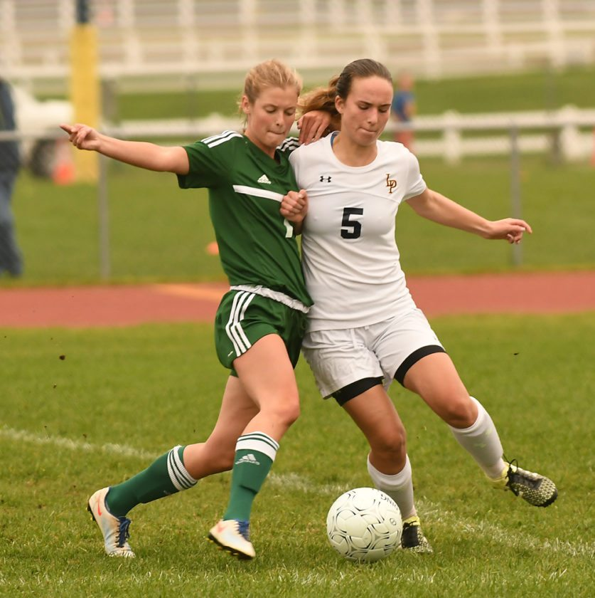 Megan Byrne of Lake Placid, right, and Chazy's Kyra Becker battle for the ball in close quarters during Tuesday's game. Byrne, a junior, assisted on the game-winning goal for the Blue Bombers. (Enterprise photo — Lou Reuter)