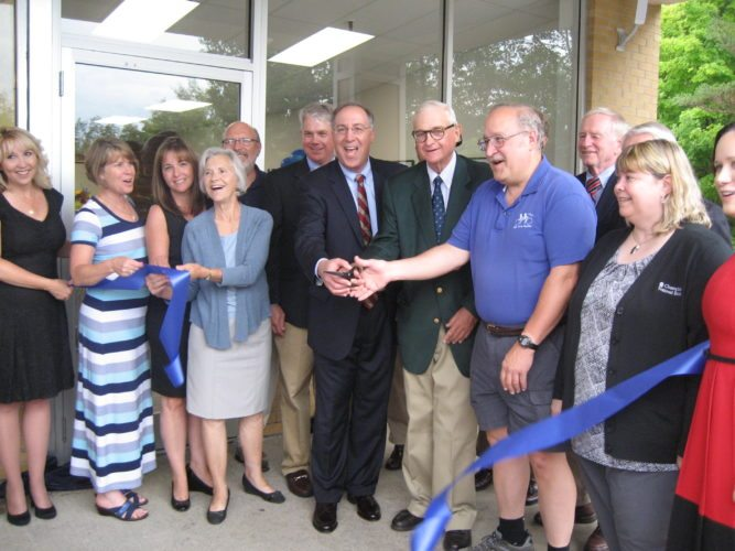 Pictured, from left, during the ribbon cutting at the new Champlain National Bank branch at 622 Lake Flower Ave. in Saranac Lake, are Lori Verzillo, Deena McCullough, Renee Darrah, Teresa Sayward, Ray Martin, Peter Paine III, Steven Cacchio, Peter Paine Jr., Rich Shapiro, Bill Kissel, Rebecca Miner and Jackie Hallock. (Photo provided)