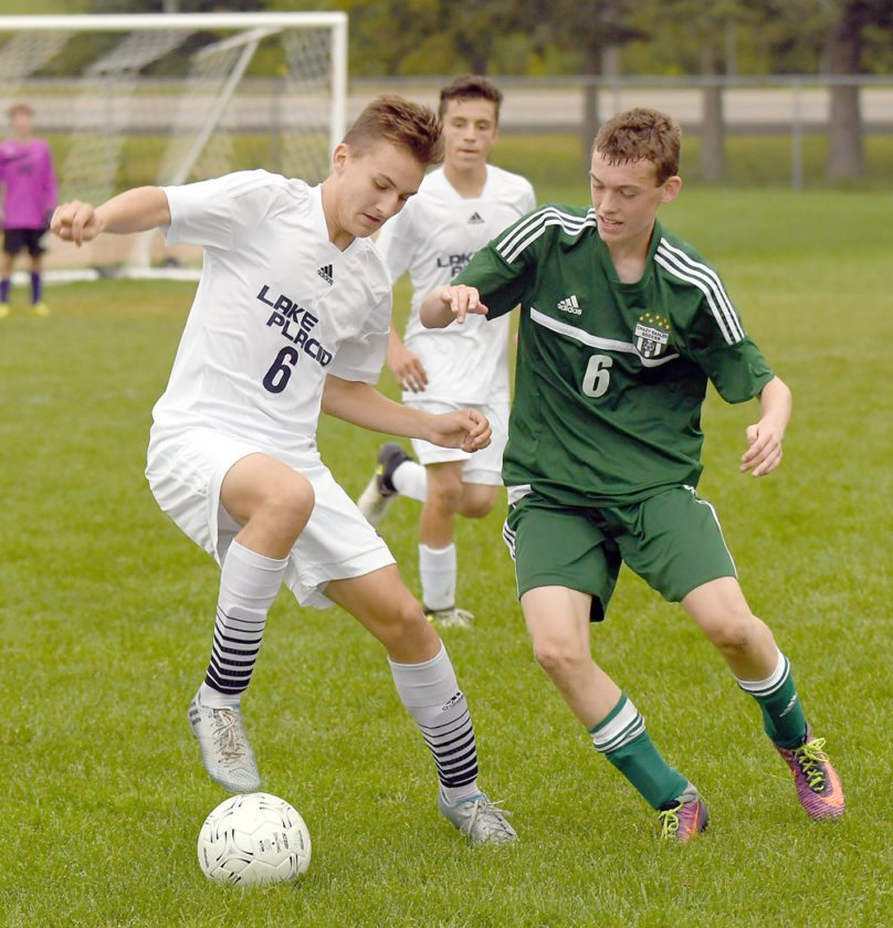 Lake Placid's Matt White controls the ball while attempting to shake off Chazy defender Heath Lucas during Wednesday's match. Also pictured in the background is Tyler Hinckley of the Blue Bombers. (Enterprise photo — Lou Reuter)