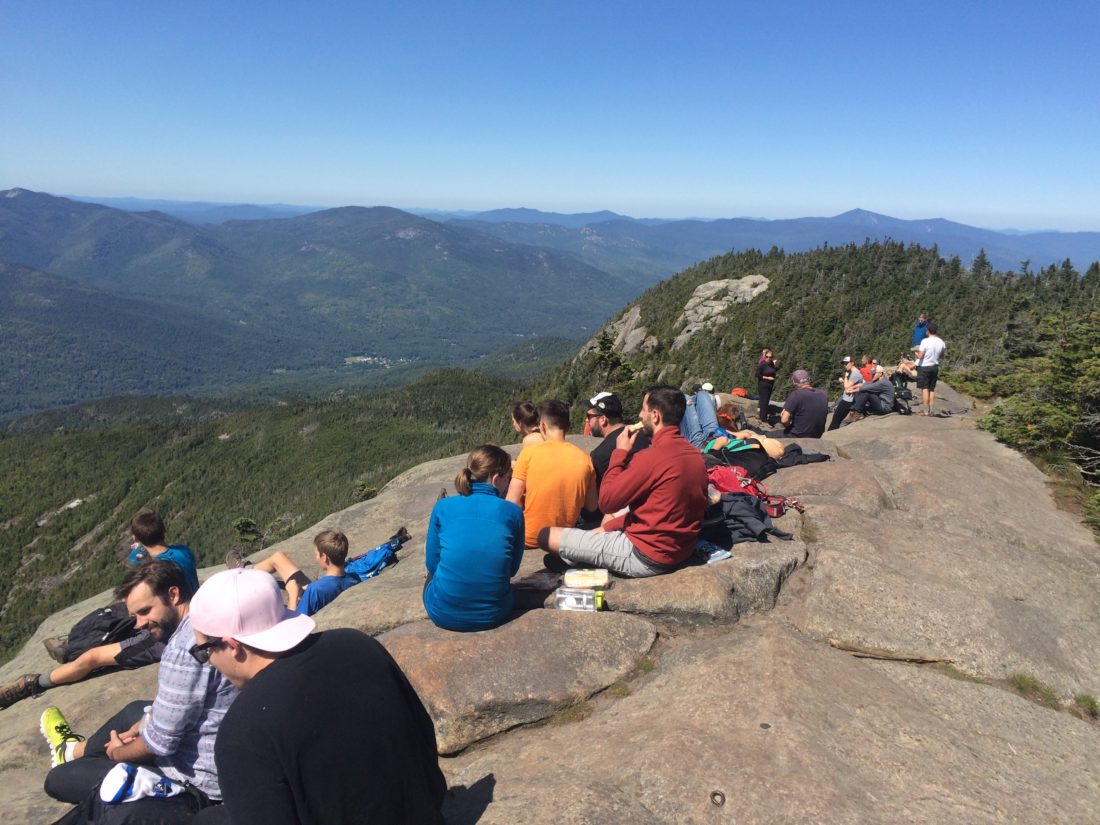 A crowd of people gazes at the High Peaks from the summit of Giant Mountain in Keene Valley Saturday. (Photo provided by ADK summit steward Vin Maresco)