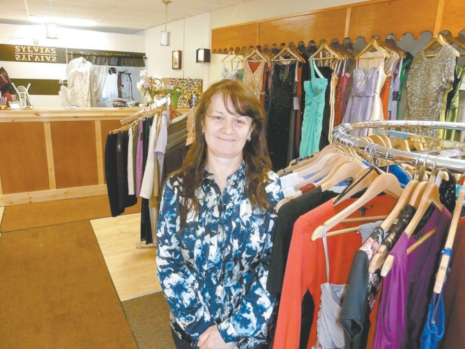 Sylvia Cecunjanin poses in the new location of her dress and tailoring shop, Sylvia's, on Broadway in the heart of downtown Saranac Lake. She moved the store this week from upper Broadway to a newly renovated storefront next to Goody Goody's toy store. The new place gives her more foot traffic, a village parking lot across the street and more space to add casual women's wear and to expand her offerings in bridal and formal dresses. The store will be closed for a few days while she goes to New York City to buy product. (Enterprise photo — Peter Crowley)