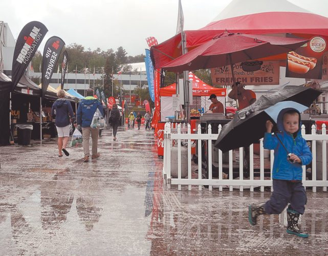 Jack Swann of Waterloo, Ontario, holds up his umbrella as he walks through the Ironman Village at the Olympic Speedskating Oval in Lake Placid on Friday evening. Jack will cheer on his father Craig Swann during the inaugural 70.3-mile half-Ironman triathlon Sunday, when Friday and Saturday's wet and soggy weather is forecast to give way to sunshine. (Enterprise photo — Antonio Olivero)