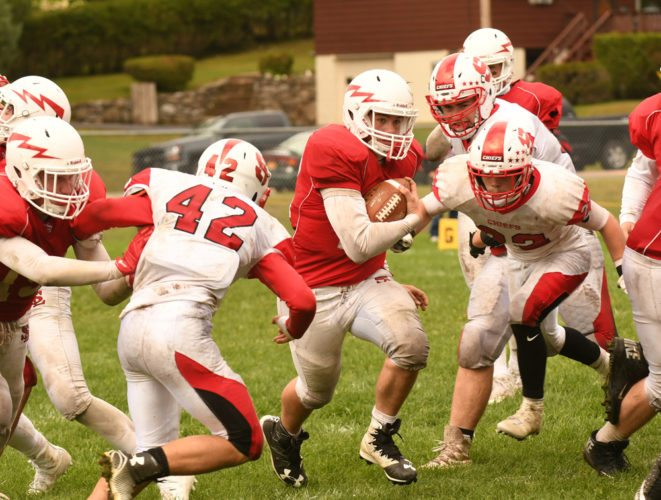 Saranac Lake quarterback DJ Morgan sprints through a gap as Saranac Central defenders Keagan Wood (42) and Johnny Devins (22) close in on the play during the first half of Saturday's game at Ken Wilson Field. (Enterprise photo — Lou Reuter)