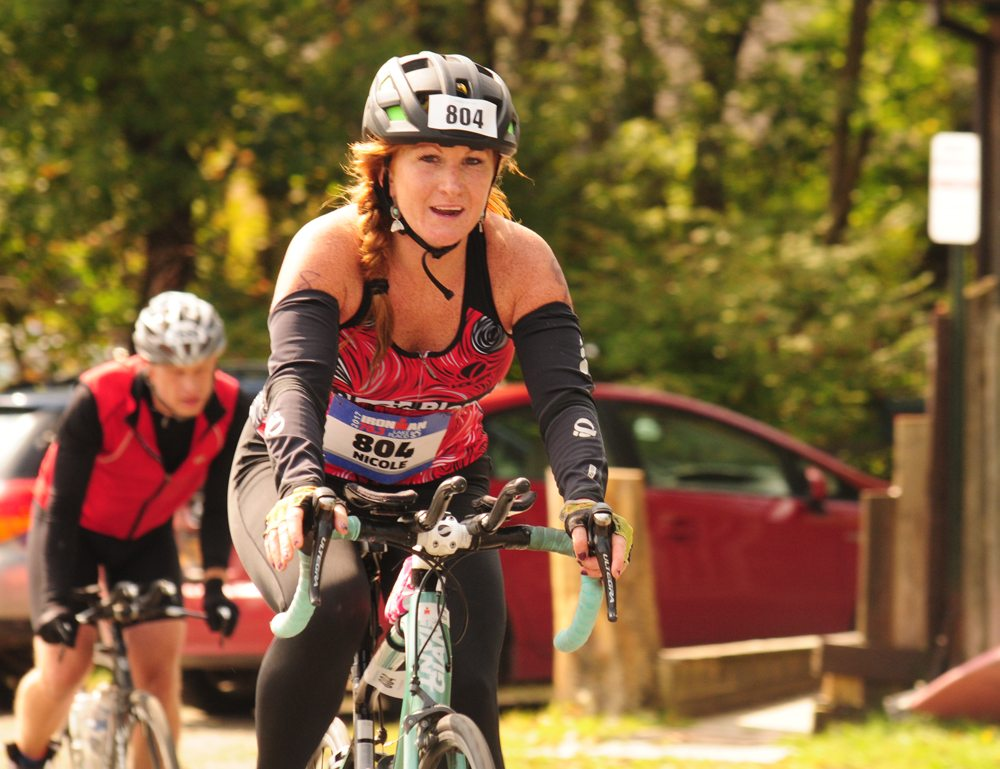 Nicole Conger, of Lake Placid, enters the stretch run of the 56-mile bike course Sunday in Lake Placid. (Enterprise photo — Morgan Ryan)