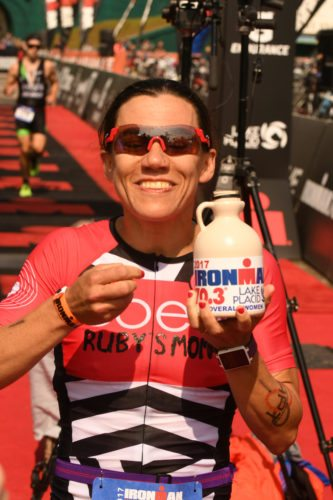 Tupper Lake's Amy Farrell enjoys a taste from the jug of maple syrup she was awarded after winning the women's overall title in Sunday's inaugural Ironman Lake Placid 70.3. The event is scheduled to be held in the Adirondacks through 2021. (Enterprise photo — Lou Reuter)