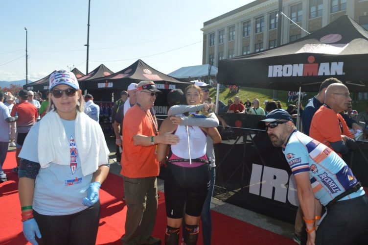 Maria Spuches Fuentes hugs her mother, Carolina Fuentes. Carolina completed the Ironman Lake Placid 70.3-mile triathlon Sunday afternoon around the same time Hurricane Irma struck Hallandale Beach, Florida, where the Fuentes live. (Enterprise photo — Antonio Olivero)